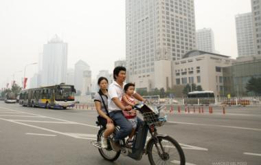 People ride a moped in Beijing