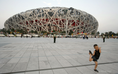 A boy plays in front of the National Stadium before the last rehearsal for the opening ceremony of the Beijing 2008 Olympic Games