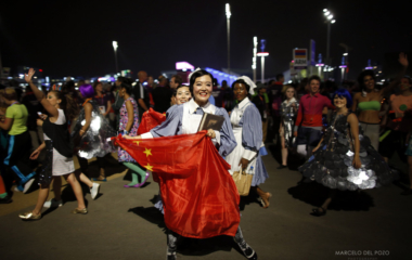 A performer holding a China flag laughs after participating in the opening ceremony of the London 2012 Olympic Games next to the Olympic Stadium at the Olympic Park in London