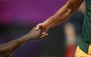South Africa's Grant Goldschmidt helps his team mate Freedom Chiya to stand up during their men's preliminary round beach volleyball match against Latvia at the London 2012 Olympic Games at Horse Guards Parade