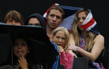 Spectators watch the men's preliminary round beach volleyball match between Poland's Mariusz Prudel and Grzegorz Fijalek against South Africa's Freedom Chiya and Grant Goldschmidt at Horse Guards Parade during the London 2012 Olympic Games