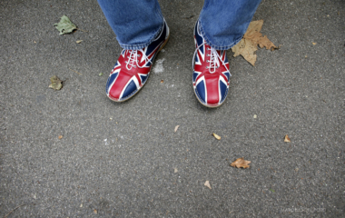A man wearing shoes bearing the Union Flag, commonly known as the Union Jack, sits outside Horse Guards Parade during the London 2012 Olympic Games
