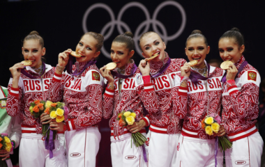 Team Russia bite their gold medals in the victory ceremony after the group all-around rhythmic gymnastics final at the London 2012 Olympic Games